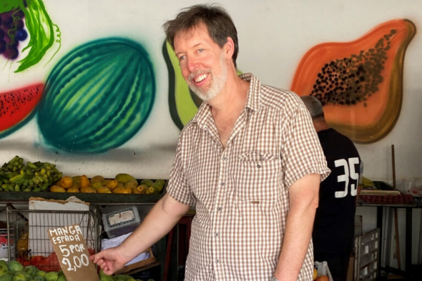 Paul Losch stands in a market in Bahia, Brazil, surrounded by green limes and holding a shopping bag.