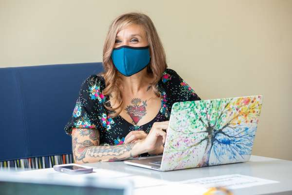 Woman with tattoos wears a mask